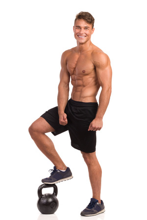 Smiling muscular man in sport shorts and sneakers posing and holding one foot on a kettlebell. Full length studio shot isolated on white. Stock Photo