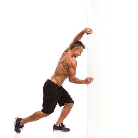 Gespierde man in de sport shorts en sneakers achter een witte muur. Full length studio shot geïsoleerd op wit. Stockfoto