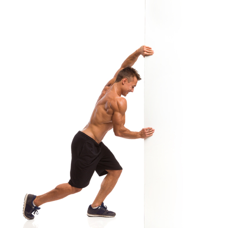 muscular: Hombre muscular en pantalones cortos de deporte y zapatillas de deporte que empuja una pared blanca. Estudio de longitud completa aislado disparo en blanco.