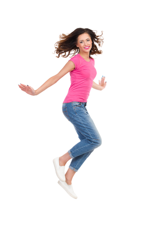 Young woman in pink shirt and jeans jumping with arms outstretched. Full length studio shot isolated on white. Standard-Bild