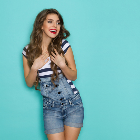 Beautiful young woman in dungarees and blue striped shirt smiling holding hands on chest and looking away. Three quarter length studio shot on teal background.
