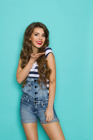 three quarter length: Beautiful smiling young woman in dungarees and blue striped shirt posing and holding hand under the head. Three quarter length studio shot on teal background.