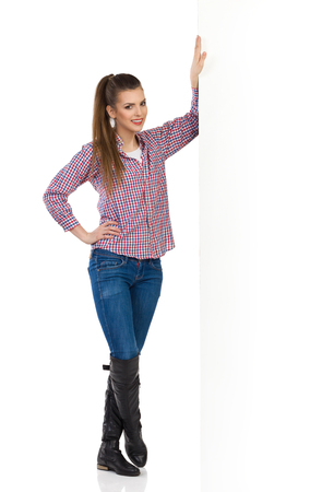 supported: Young woman in jeans, black boots and lumberjack shirt standing based on a big banner . Full length studio shot isolated on white.