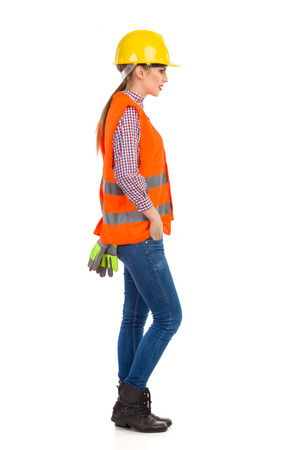 lumberjack shirt: Young woman in orange reflective vest, lumberjack shirt, jeans and black boots,  standing in yellow hardhat and holding hand in pocket, side view. Full length studio shot isolated on white. Stock Photo