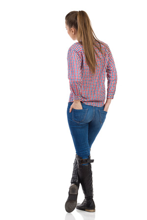 Young woman in jeans, black boots and lumberjack shirt standing with hands in back pocket. Rear view. Full length studio shot isolated on white. Stockfoto