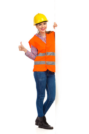 reflective vest: Smiling beautiful young woman in yellow hardhat, orange reflective vest and lumberjack shirt standing behind big white banner and showing thumb up. Full length studio shot isolated on white.