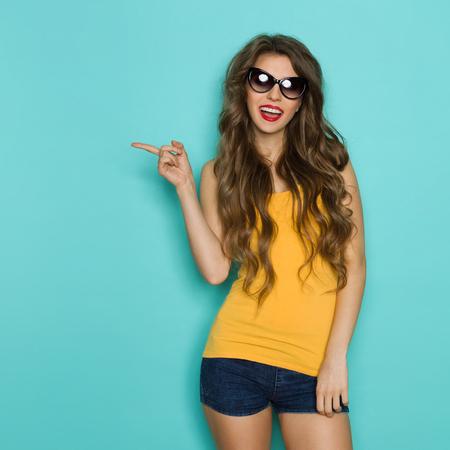아름 다운 젊은 여자 선글라스, 청바지 반바지와 노란색 셔츠 복사본 공간에서 가리키고 얘기. 3 분기 길이 스튜디오 청록 배경에 쐈 어. 스톡 콘텐츠 - 52222477