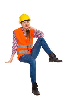 lumberjack shirt: Cheerful young woman in orange reflective vest, lumberjack shirt, jeans, black boots, sitting and holding hand on chin. Full length studio shot isolated on white.