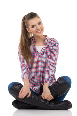 lumberjack shirt: Smiling young woman in lumberjack shirt, jeans and black boots sitting on a floor with legs crossed and looking at camera. Full length studio shot isolated on white.
