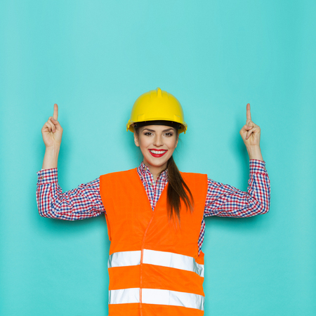 reflective: Smiling young woman in orange reflective vest and yellow hardhat pointing up and looking at camera. Waist up studio shot on turquoise background.