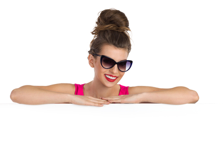 messy hair: Smiling young woman in sunglasses with big messy hair bun leans a white banner and looking at camera. Head and shoulders studio shot isolated on white.