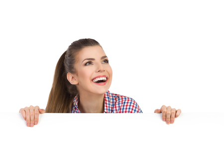 leans: Smiling beautiful smiling young woman in glasses and lumberjack shirt leans on a white banner and looking at camera. Head and shoulders studio shot isolated on white. Stock Photo