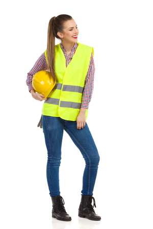 reflective vest: Smiling young woman in lime green reflective vest holding yellow hardhat under her arm and looking away. Full length studio shot isolated on white.