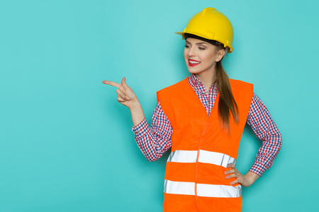 reflective vest: Smiling young woman in orange reflective vest and yellow hardhat pointing up and looking at camera. Waist up studio shot on turquoise background.