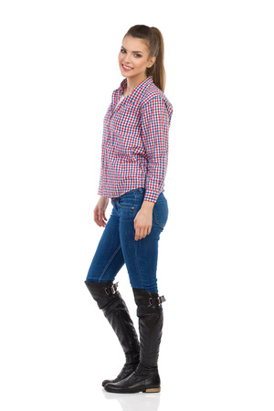 lumberjack shirt: Young woman in jeans, black boots and lumberjack shirt standing and looking at camera. Side view. Full length studio shot isolated on white.