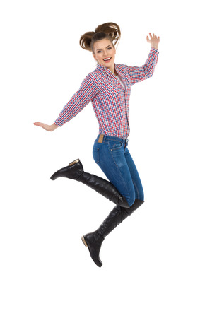 lumberjack shirt: Young woman in lumberjack shirt, jeans and black boots jumping with arms outstretched. Full length studio shot isolated on white.