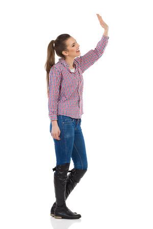 profile view: Young woman in jeans, black boots and lumberjack shirt standing with arm raised and waving. Side view. Full length studio shot isolated on white. Stock Photo