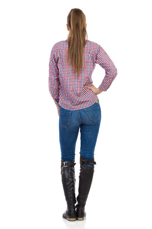 lumberjack shirt: Young woman in jeans, black boots and lumberjack shirt standing with hand on hip. Rear view. Full length studio shot isolated on white. Stock Photo
