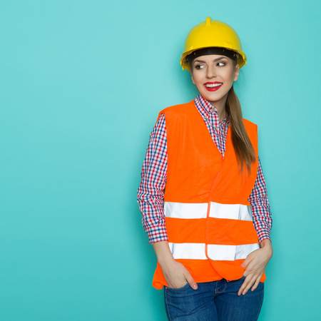 reflective vest: Beautiful young woman in orange reflective vest, yellow hardhat and jeans posing with hands in pockets, looking at teal copy space and smiling. Three quarter length studio shot on turquoise background.