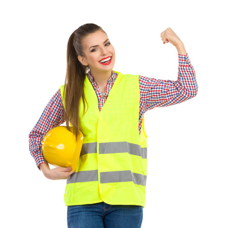reflective vest: Smiling young woman in lime green reflective vest holding yellow hardhat under her arm, looking at camera and rising fist. Three quarter length length studio shot isolated on white.
