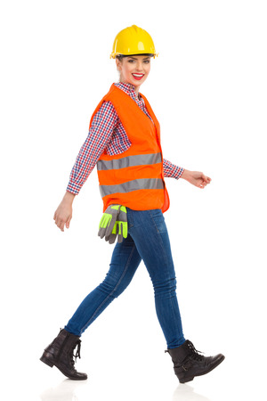 reflective vest: Smiling young woman in orange reflective vest, lumberjack shirt, jeans, black boots,walking and looking at camera. Side view. Full length studio shot isolated on white. Stock Photo