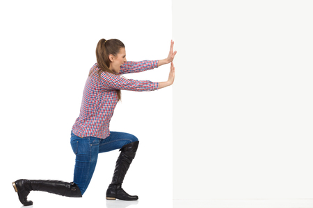 Young woman in jeans, black boots and lumberjack shirt pushing a white wall and shouting. Side view, full length studio shot isolated on white. Standard-Bild