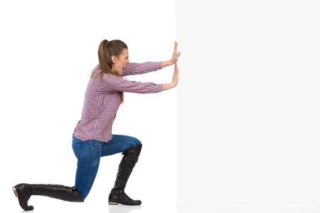Mujer joven en pantalones vaqueros, botas negras y camisa de leñador empujando una pared blanca y gritando. Vista lateral, tiro de estudio de longitud completa aislado en blanco.