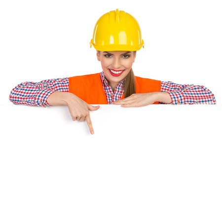 warning vest: Beautiful smiling young woman in yellow hardhat, orange reflective vest and lumberjack shirt posing behind big white banner, pointing down and looking at camera. Studio shot isolated on white.