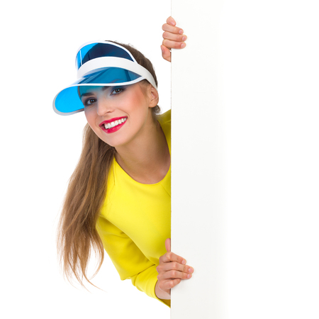 visor: Smiling young woman in yellow top and blue sun visor peeking behind big white banner. Waist up studio shot isolated on white. Stock Photo