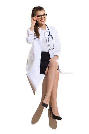 Smiling young woman in glasses, white coat, black skirt and highheels sitting with legs crossed on a big white banner. Full length studio shot isolated on white.