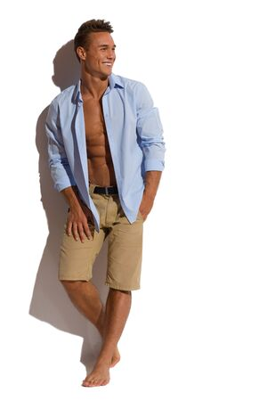 Handsome smiling young man in beige shorts and blue unbuttoned shirt standing relaxed against sunny wall and looking away Full length studio shot isolated on white.