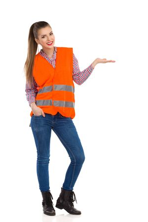reflective: Smiling girl in orange reflective vest, lumberjack shirt, jeans and black boots showing something with open hand. Full length studio shot isolated on white. Stock Photo