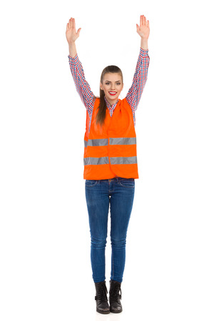 lumberjack shirt: Smiling young woman in orange reflective vest, lumberjack shirt, jeans and black boots, standing with raised arms. Front view. Full length studio shot isolated on white. Stock Photo