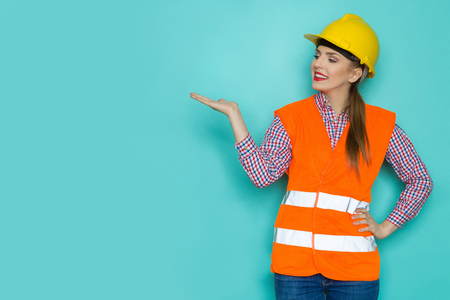 Cheerful young woman in orange reflective vest, yellow hardhat and jeans presenting and looking at teal copy space. Three quarter length studio shot on turquoise background.