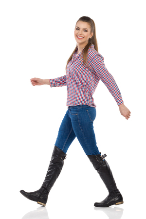 striding: Smiling young woman in jeans, black boots and lumberjack shirt walking and looking at camera. Side view, full length studio shot isolated on white. Stock Photo