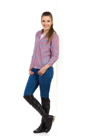 leans: Young woman in jeans, black boots and lumberjack shirt leans on white wall and looking at camera. Side view. Full length studio shot isolated on white. Stock Photo