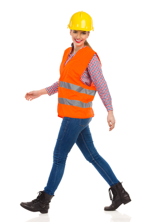 lumberjack shirt: Smiling young woman in orange reflective vest, lumberjack shirt, jeans, black boots,walking and looking at camera. Side view. Full length studio shot isolated on white. Stock Photo