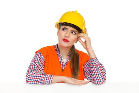 reflective vest: Young woman in yellow hardhat, orange reflective vest and lumberjack shirt leans on a white banner, scrathing head, looking up and thinking. Studio shot isolated on white.