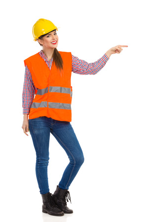 reflective vest: Smiling young woman in yellow hardhat, orange reflective vest, lumberjack shirt, jeans and black boots, pointing and looking at camera. Full length studio shot isolated on white.