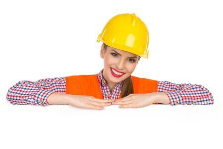 lumberjack shirt: Beautiful smiling young woman in yellow hardhat, orange reflective vest and lumberjack shirt posing behind big white poster and looking at camera. Studio shot isolated on white. Stock Photo
