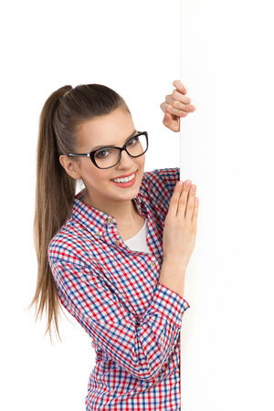 lumberjack shirt: Smiling beautiful young woman in glasses and lumberjack shirt standing behind white banner and holding it. Waist up studio shot isolated on white.