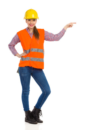 lumberjack shirt: Cheerful beautiful woman in yellow hardhat, orange reflective vest, lumberjack shirt, jeans and black boots, pointing and looking at camera. Full length studio shot isolated on white. Stock Photo