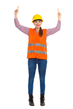 reflective vest: Smiling young woman in yellow hardhat, orange reflective vest, lumberjack shirt, jeans and black boots, raising arms, pointing up and looking at camera. Full length studio shot isolated on white.