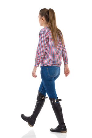 lumberjack shirt: Young woman with long hair in jeans, black boots and lumberjack shirt walking. Rear side view, full length studio shot isolated on white. Stock Photo