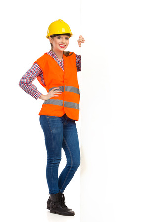 lumberjack shirt: Smiling young woman in yellow hardhat, orange reflective vest and lumberjack shirt posing with big white banner. Full length studio shot isolated on white.