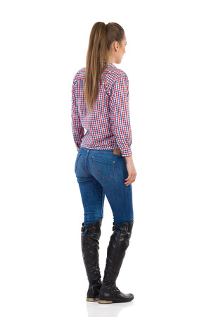 lumberjack shirt: Young woman standing in jeans, black boots and lumberjack shirt. Rear side view. Full length studio shot isolated on white.