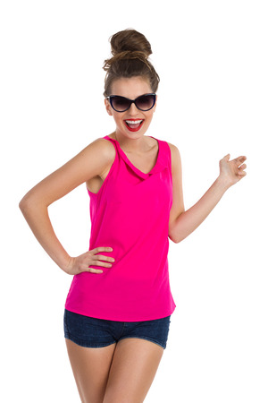 topknot: Shouting young woman with messy hair bun in sunglasses, pink shirt, jeans shorts and pink sneakers posing with hand on hip. Three quarter length length studio shot isolated on white.