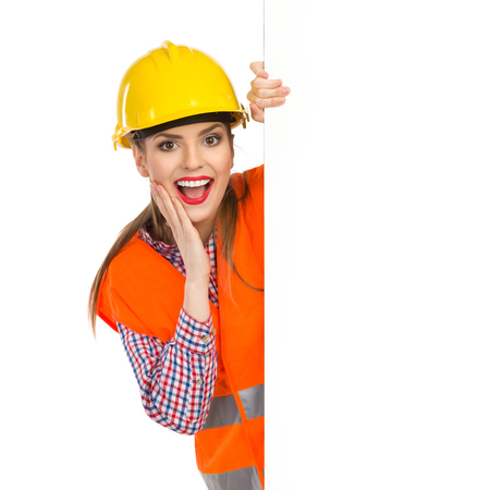 reflective vest: Excited young woman in yellow hardhat, orange reflective vest and lumberjack shirt posing with big banner with mouth open and hand on chin. Waist up studio shot isolated on white.