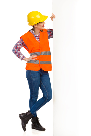 lumberjack shirt: Smiling young woman in yellow hardhat, orange reflective vest and lumberjack shirt standing close to a big banner and reading. Full length studio shot isolated on white.