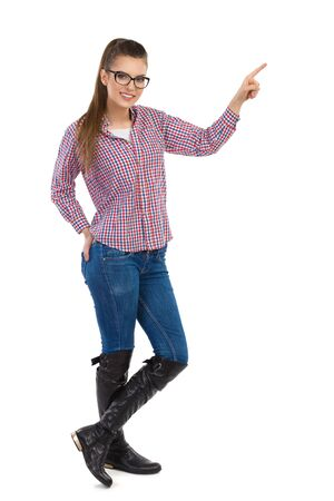 lumberjack shirt: Smiling young woman in glasses, lumberjack shirt, jeans, and black boots, pointing and looking at camera. Full length studio shot isolated on white.